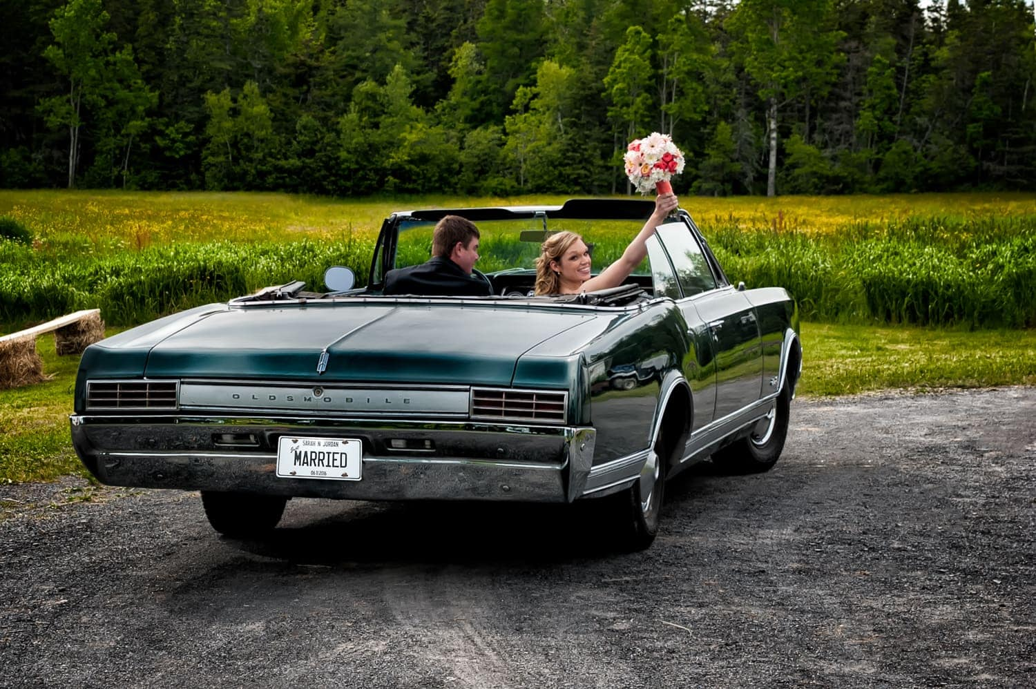 bride and groom in antique car driving away