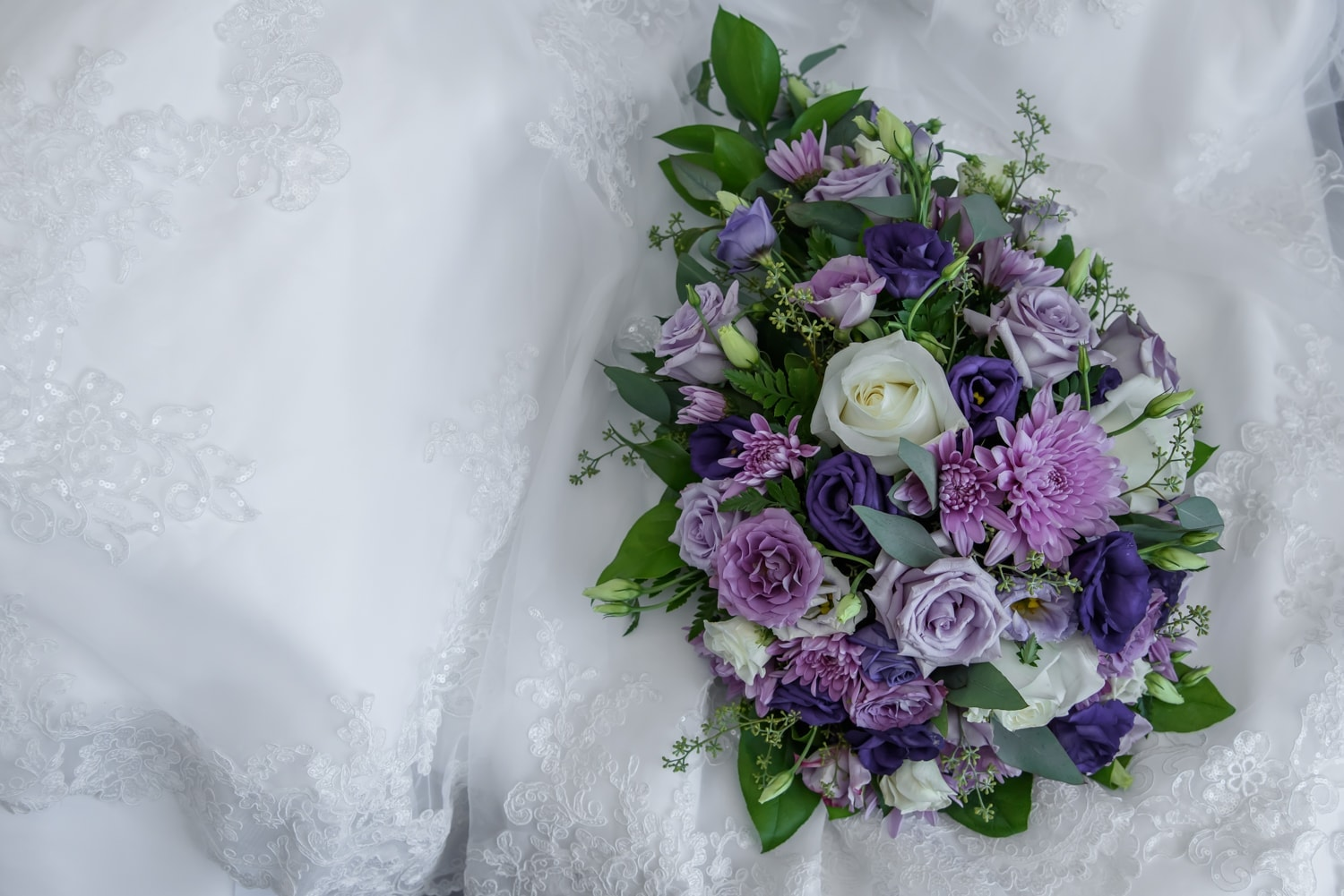 A real flower wedding bridal bouquet with ivory and purple flowers.