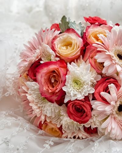 A wedding bridal bouquet with shades of pink roses and ivory flowers.