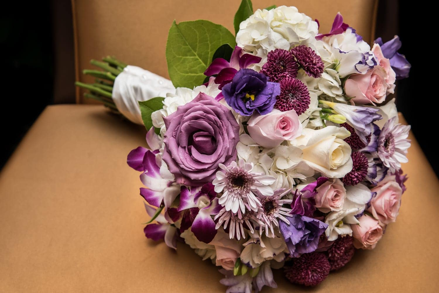 Real flowers in a wedding bridal bouquet of ivory, purple and pink flowers.