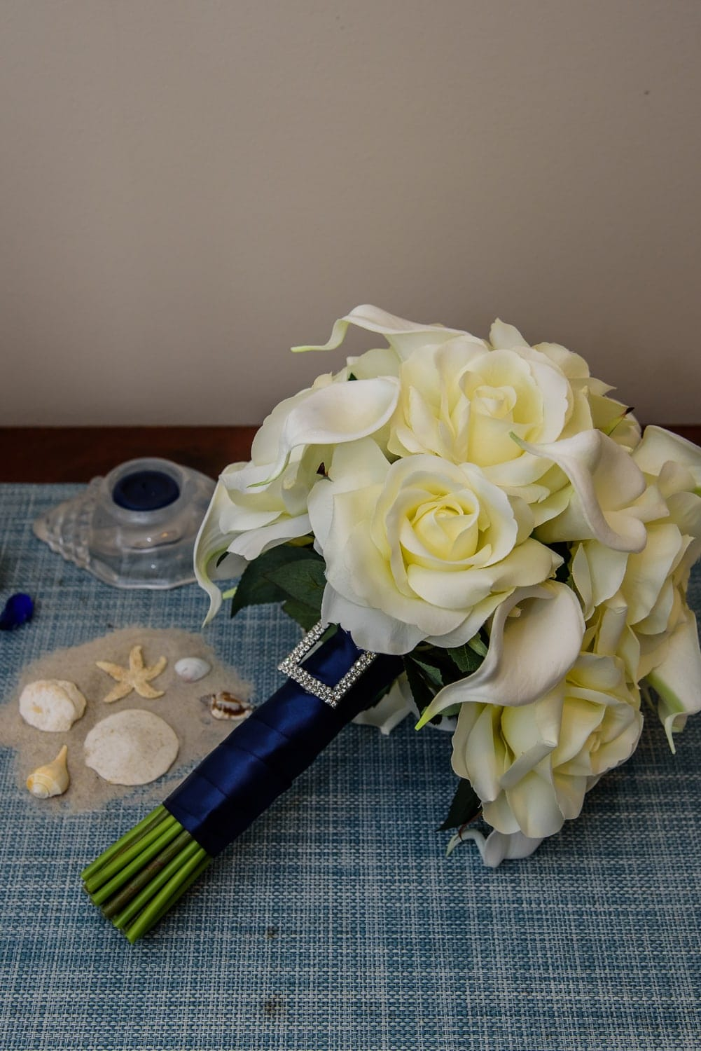 A wedding bridal bouquet of ivory roses and navy embellishments.