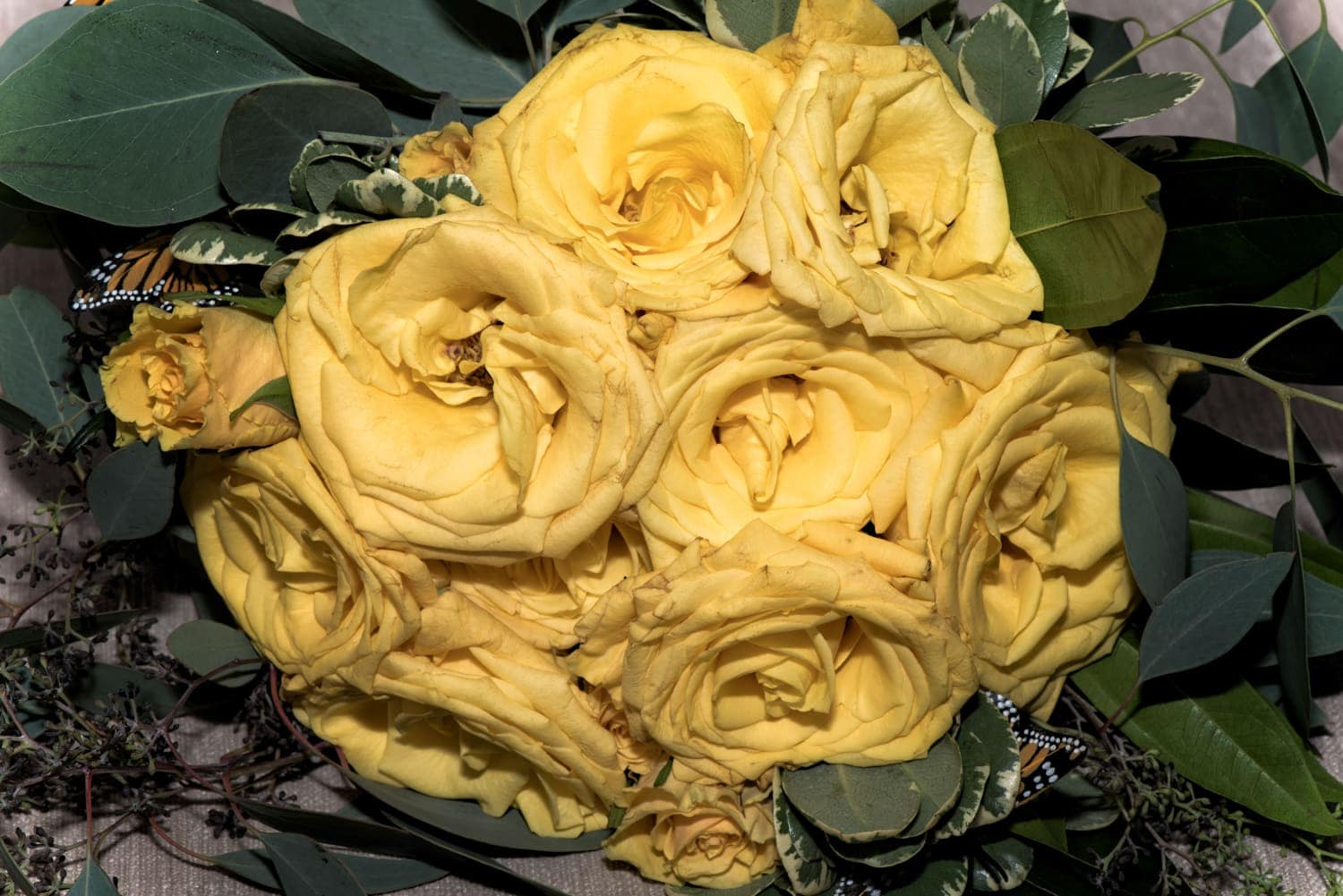 A wedding bridal bouquet with yellow roses and accented with butterflies.