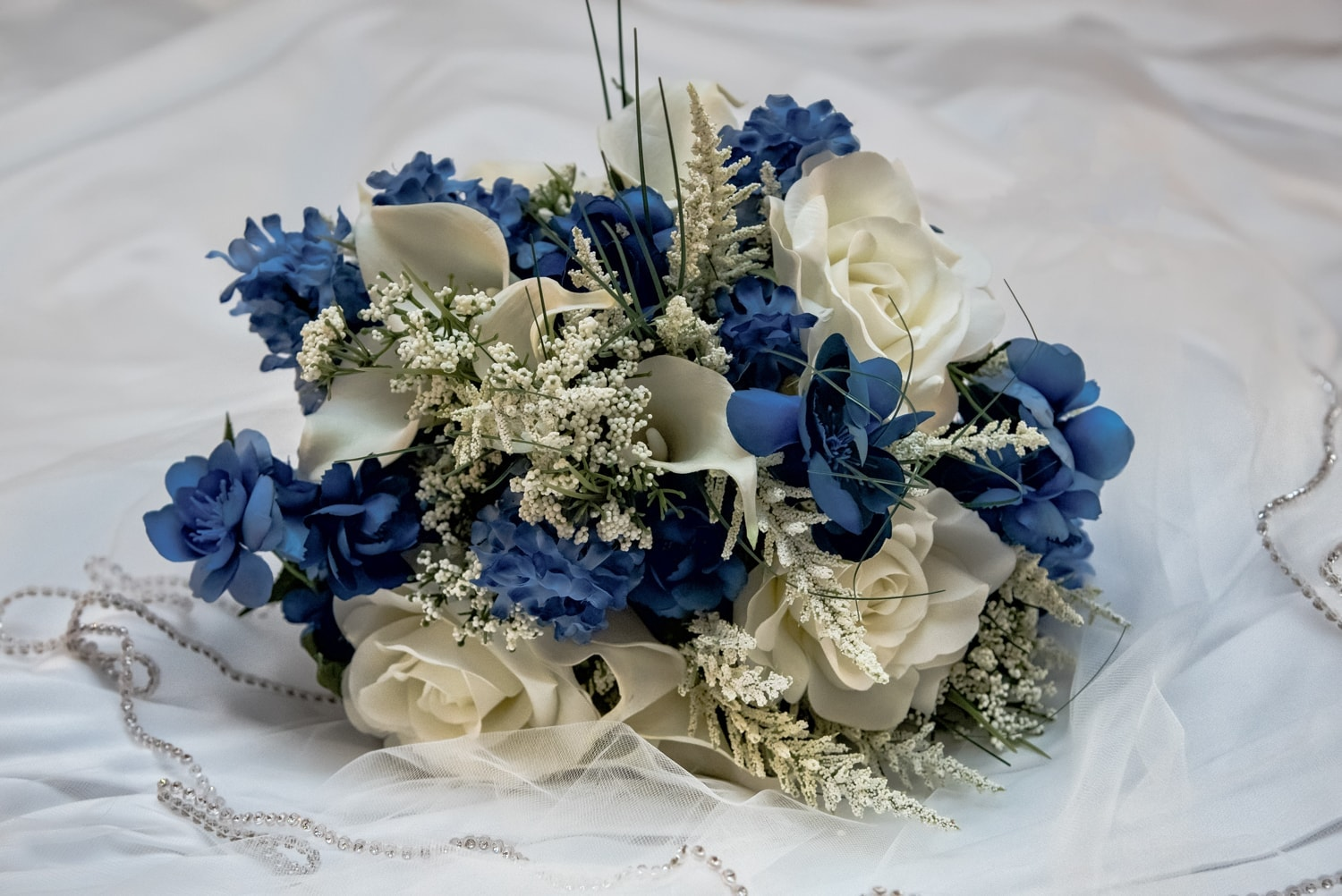A silk fake flower wedding bridal bouquet in ivory and navy blue.