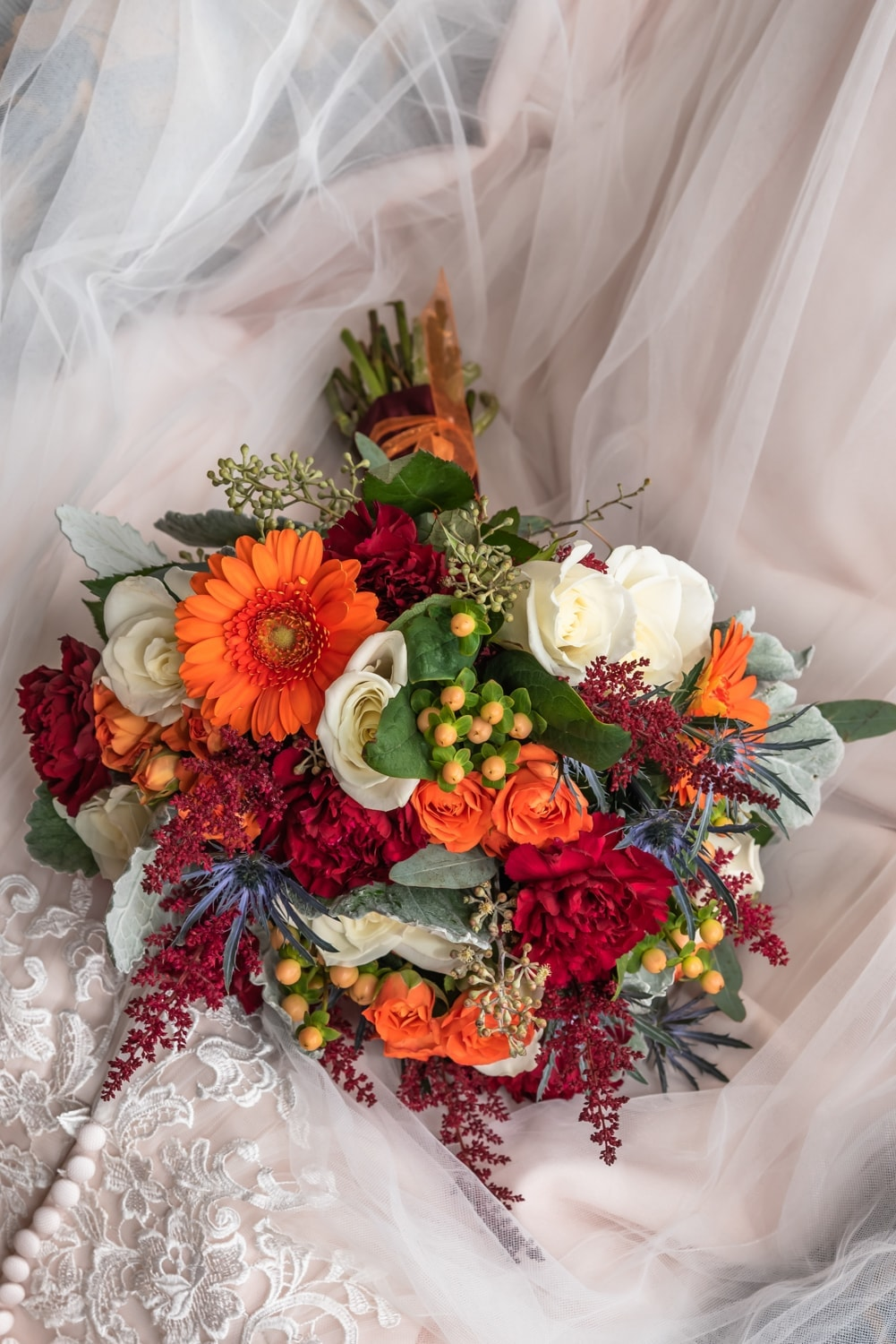 A beautiful wedding bridal bouquet of orange, wines and ivory colored flowers.