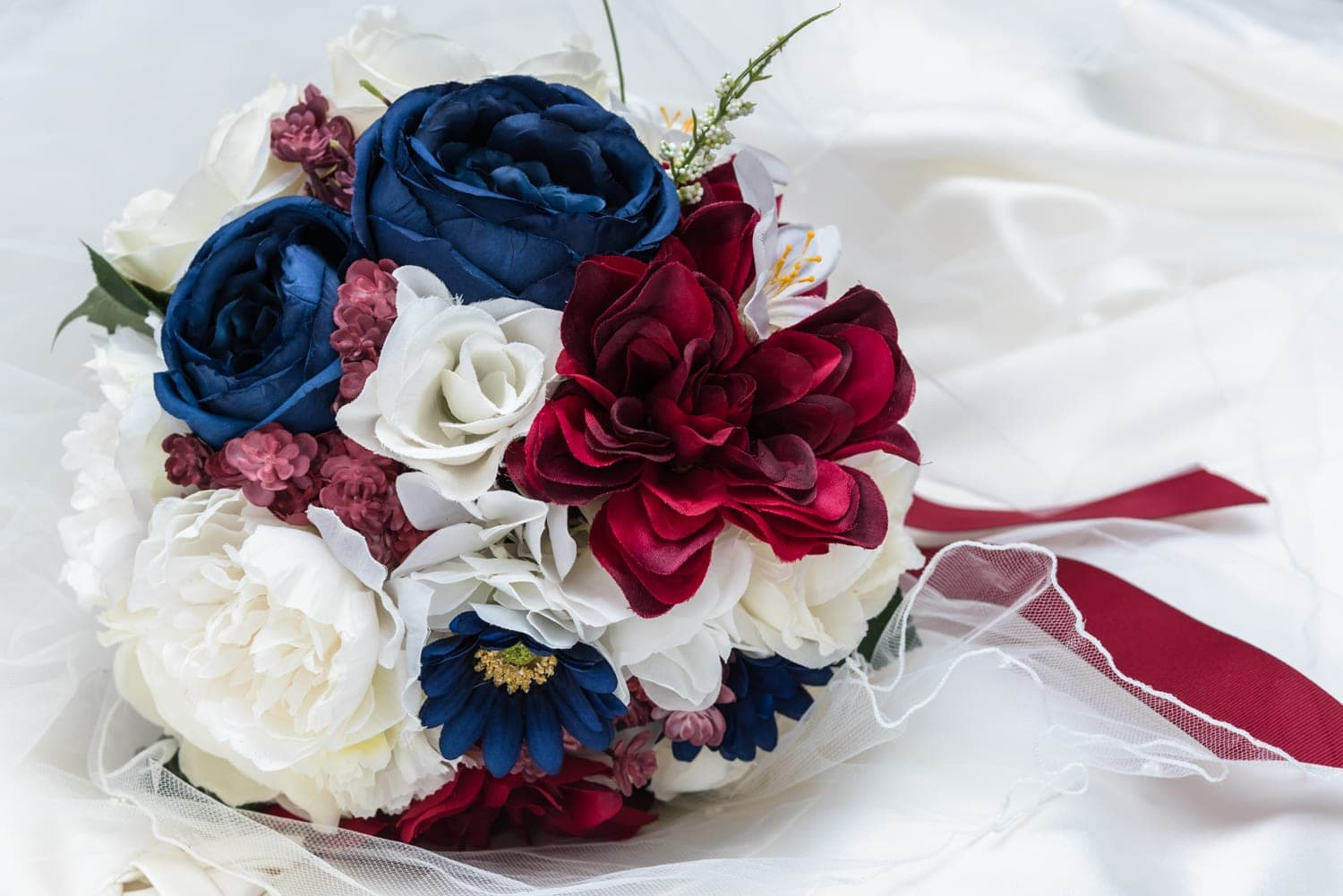 A navy, red and white arrangement of silk fake flowers in a wedding bridal bouquet.