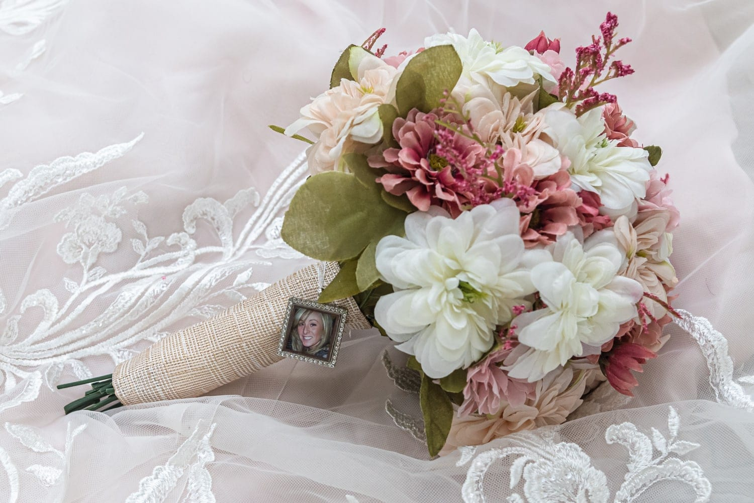 A silk flower arrangement of white, pink and green in a wedding bridal bouquet.