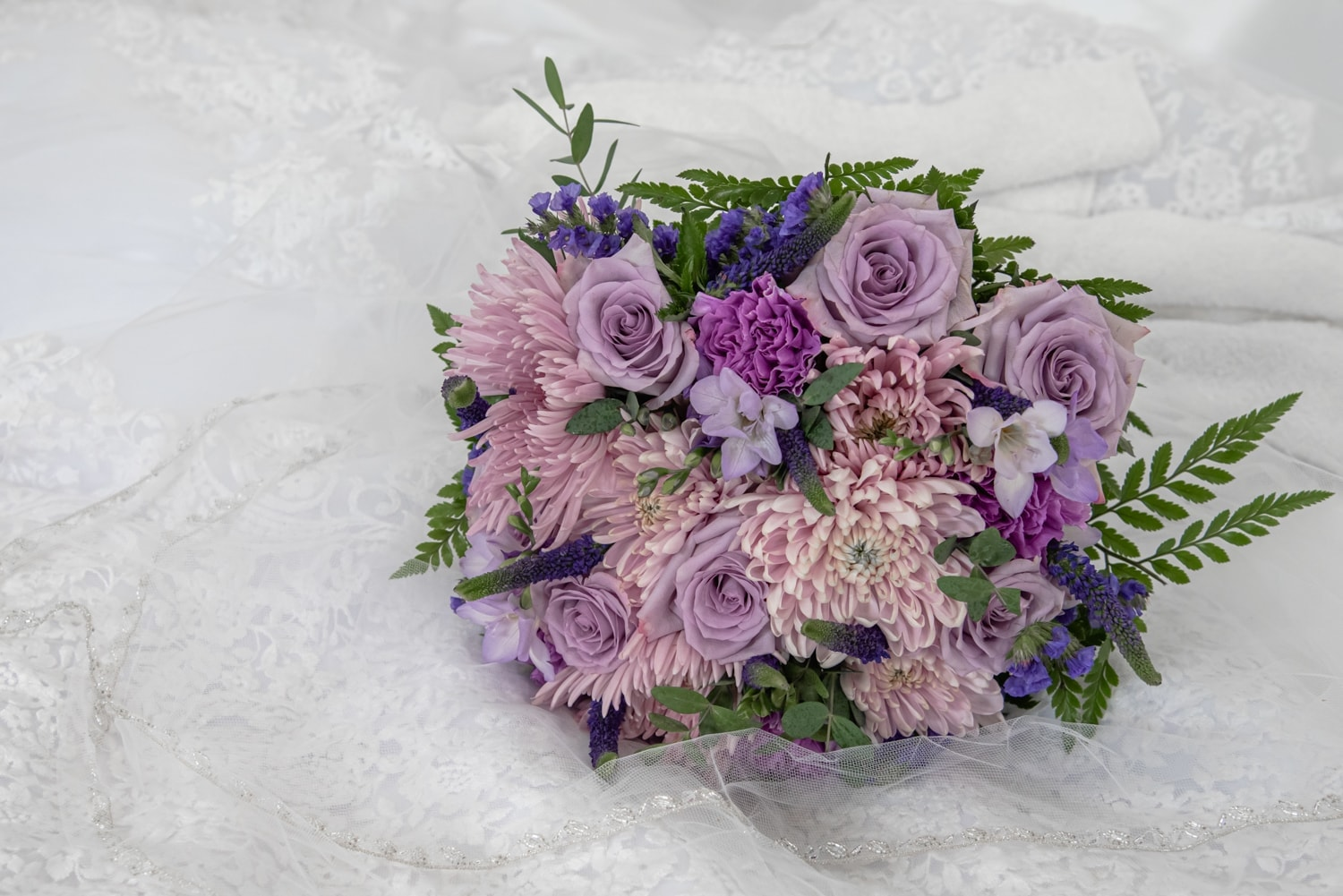 An arrangement of purple and pink flowers in a wedding bridal bouquet.