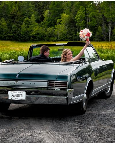 The bride and groom drive away from their wedding ceremony in an antique car headed for their reception at the Brooklyn Civic Center in Newport, NS.