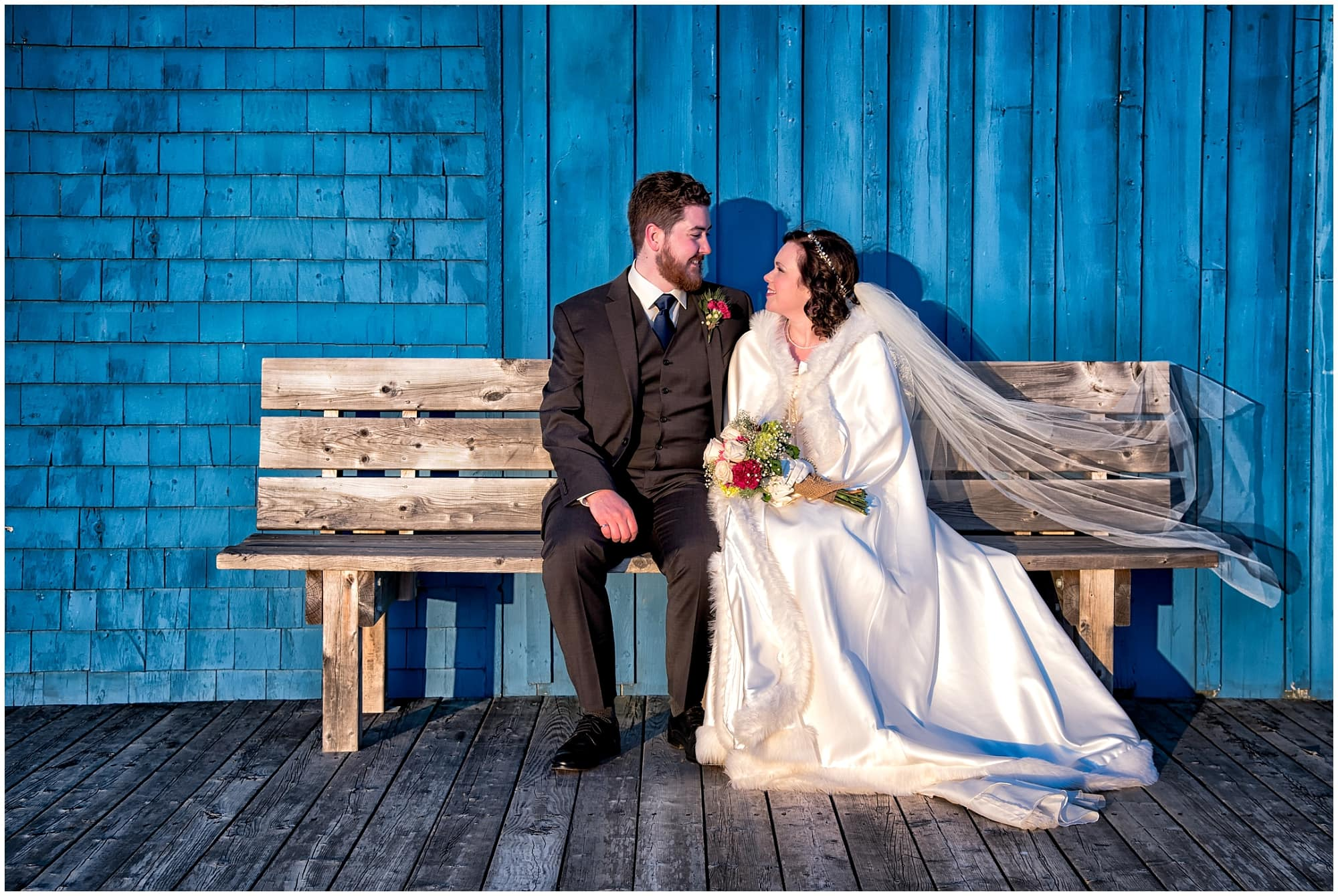 The bride and groom pose on a wooden bench for wedding photos at Fisherman's Cove in Eastern Passage, NS.