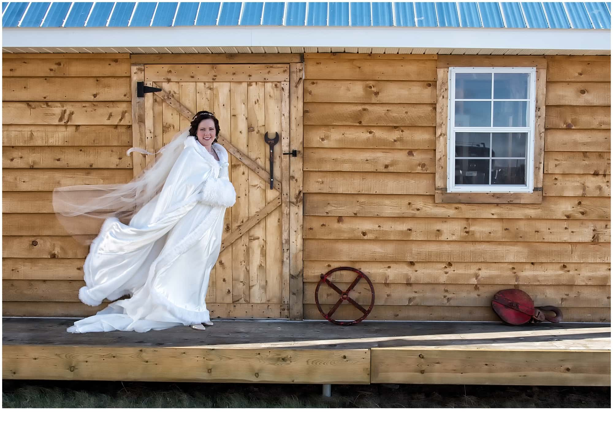 The bride ready for her winter wedding in her wedding dress and cape with winter muff.