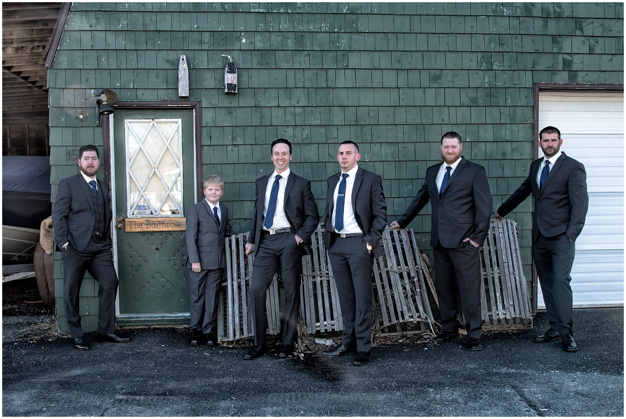 The groom with groomsmen posing for wedding photos among the fishermen shacks and lobster traps at Fisherman's Cove in Eastern Passage NS.