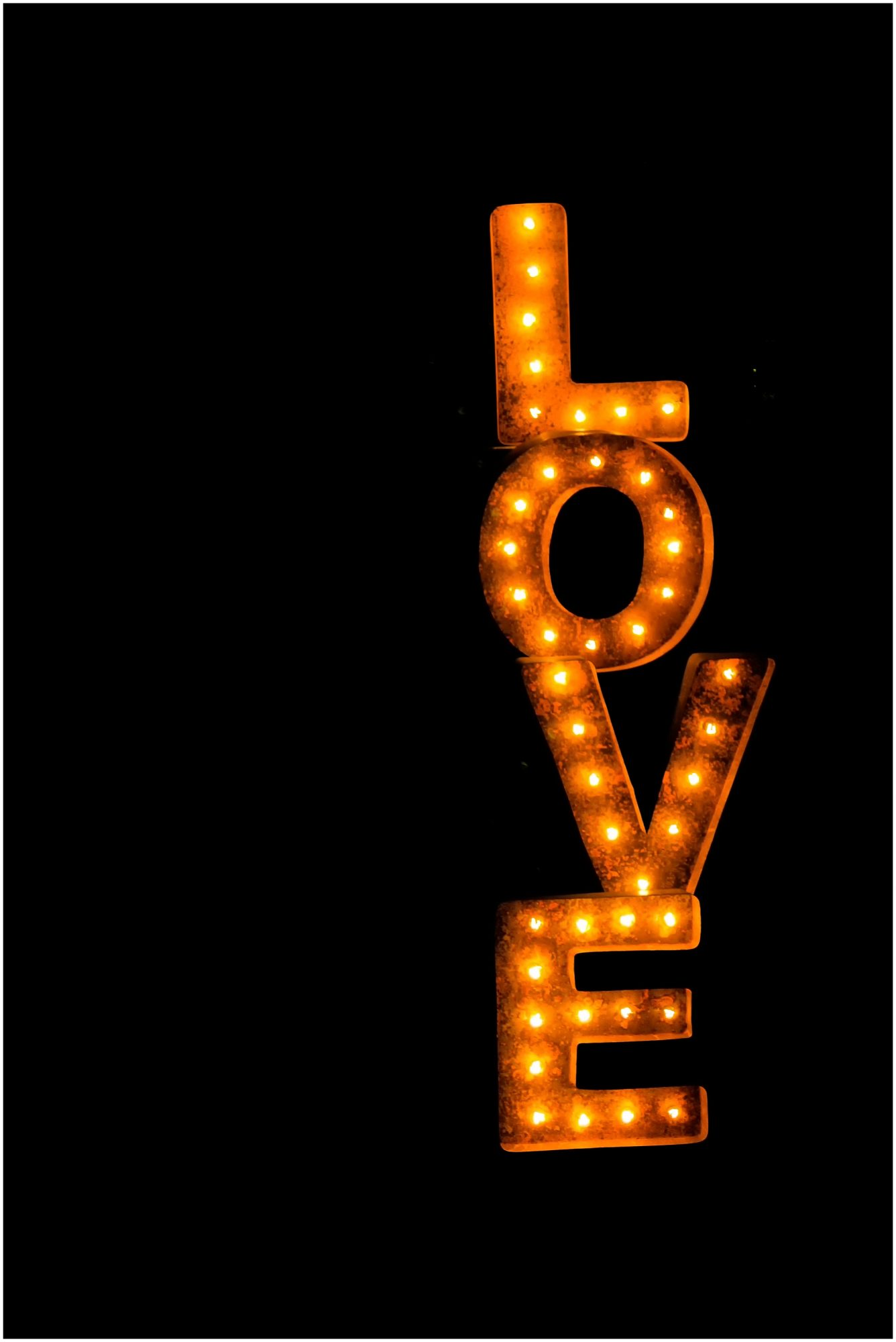 Marquee lights love word lit up in the dark.