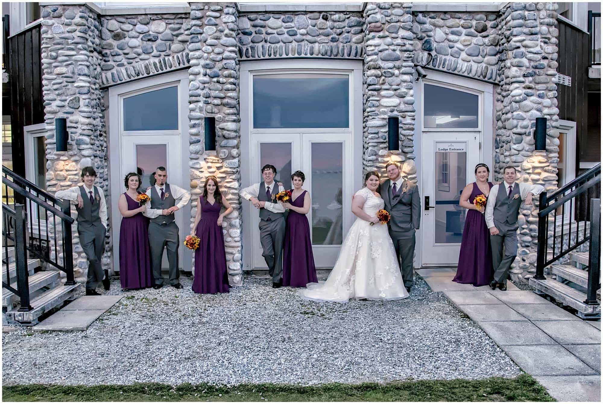 The bride and groom pose with their wedding party for wedding photos at White Point Beach Resort in Nova Scotia.