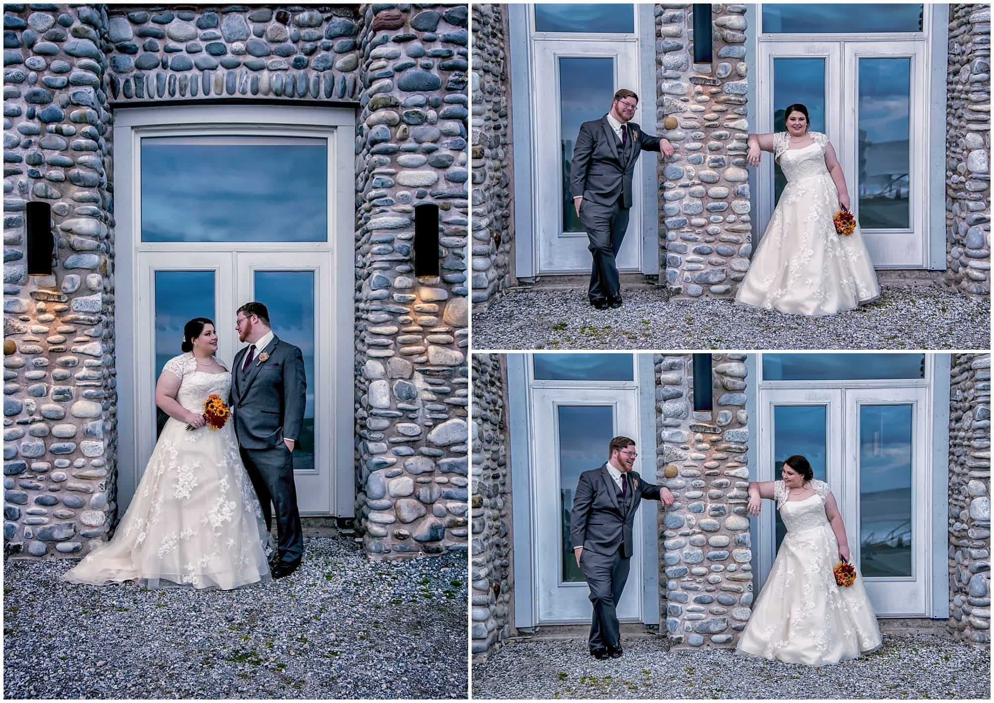 The bride and groom pose in front of stone work on the back of the Main Lodge at White Point for their wedding photos.