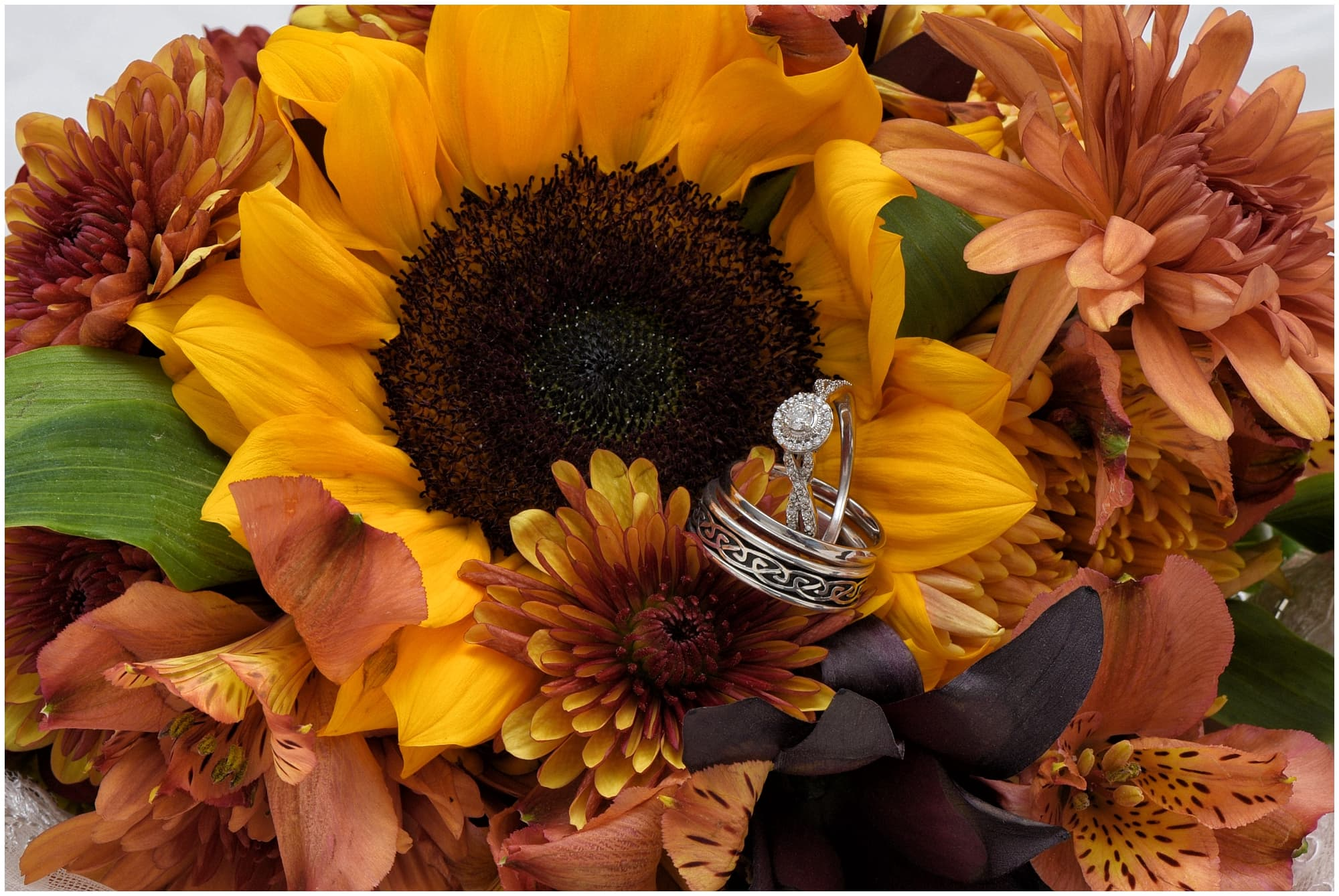 A beautiful sunflower bridal bouquet with wedding rings.