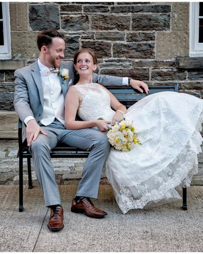 The bride and groom sitting on a rod iron bench at the Historic Properties in Halifax, NS.