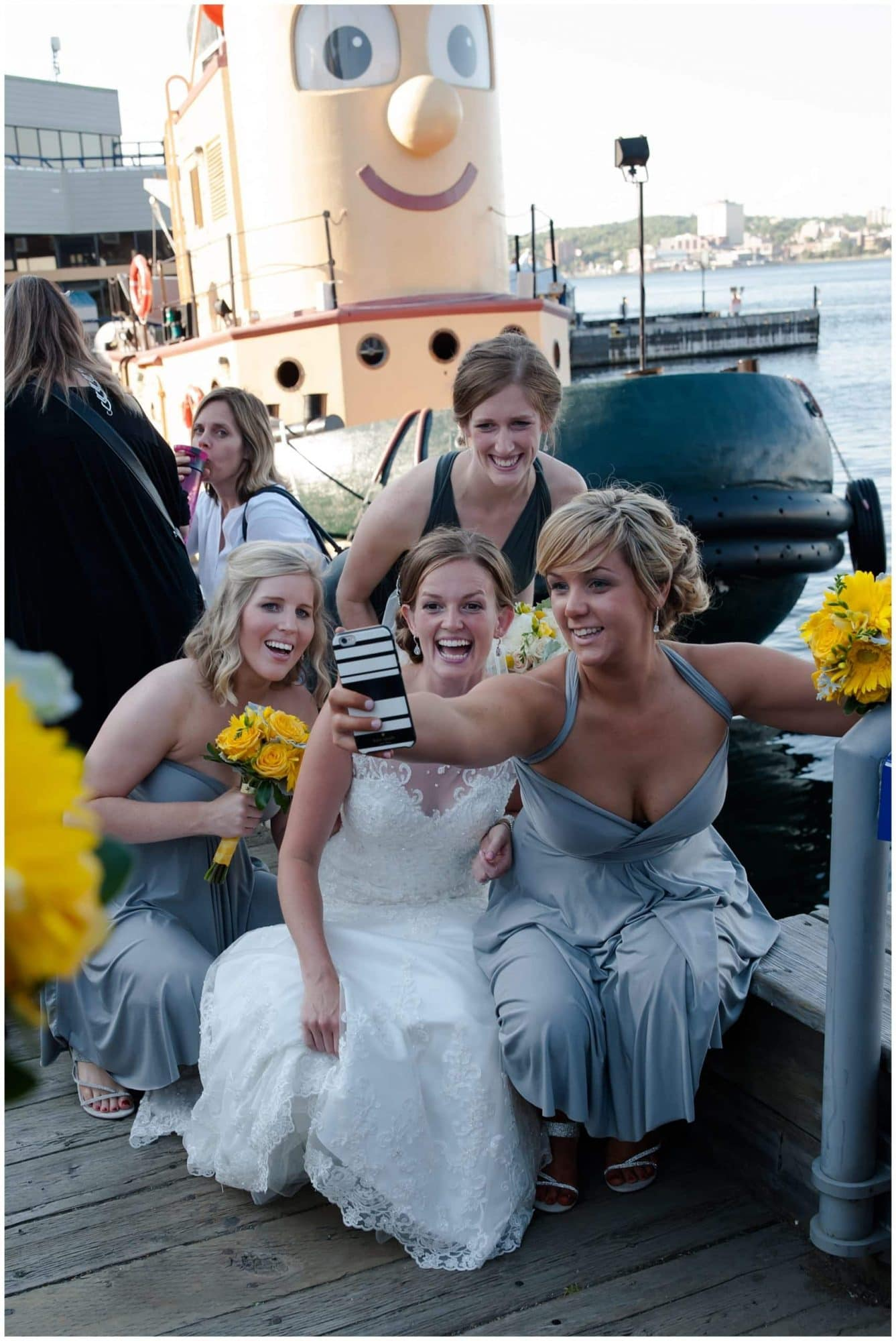 The bride snaps a selfie of her and her bridesmaids infront of Theodore the tug boat in Halifax, NS.