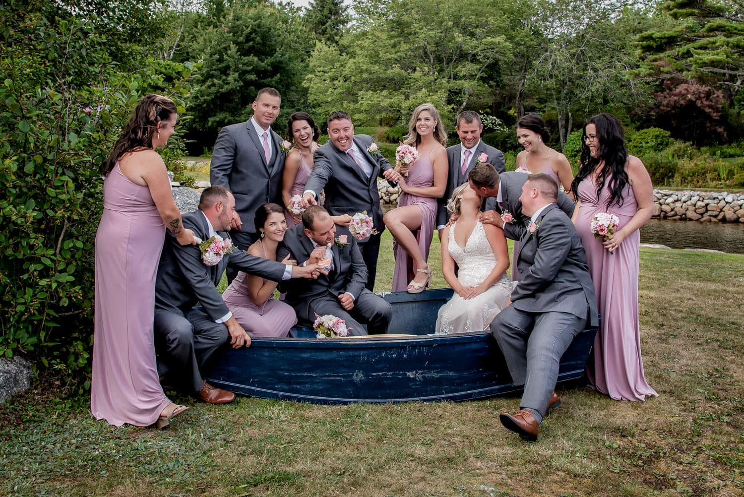 The bride and groom with the wedding party posing for wedding photos in a boat, bride kissing a groomsmen and groom drinking alcohol during a backyard wedding in Halifax.