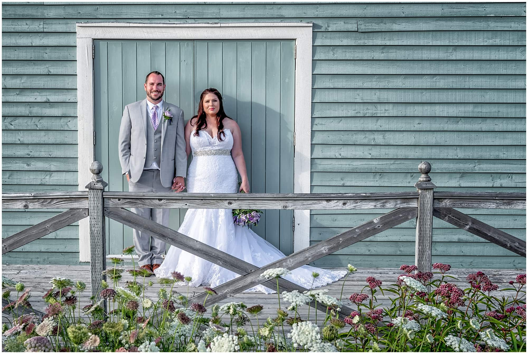 The bride and groom pose for wedding photos at their White Point wedding against a rustic barn style building.
