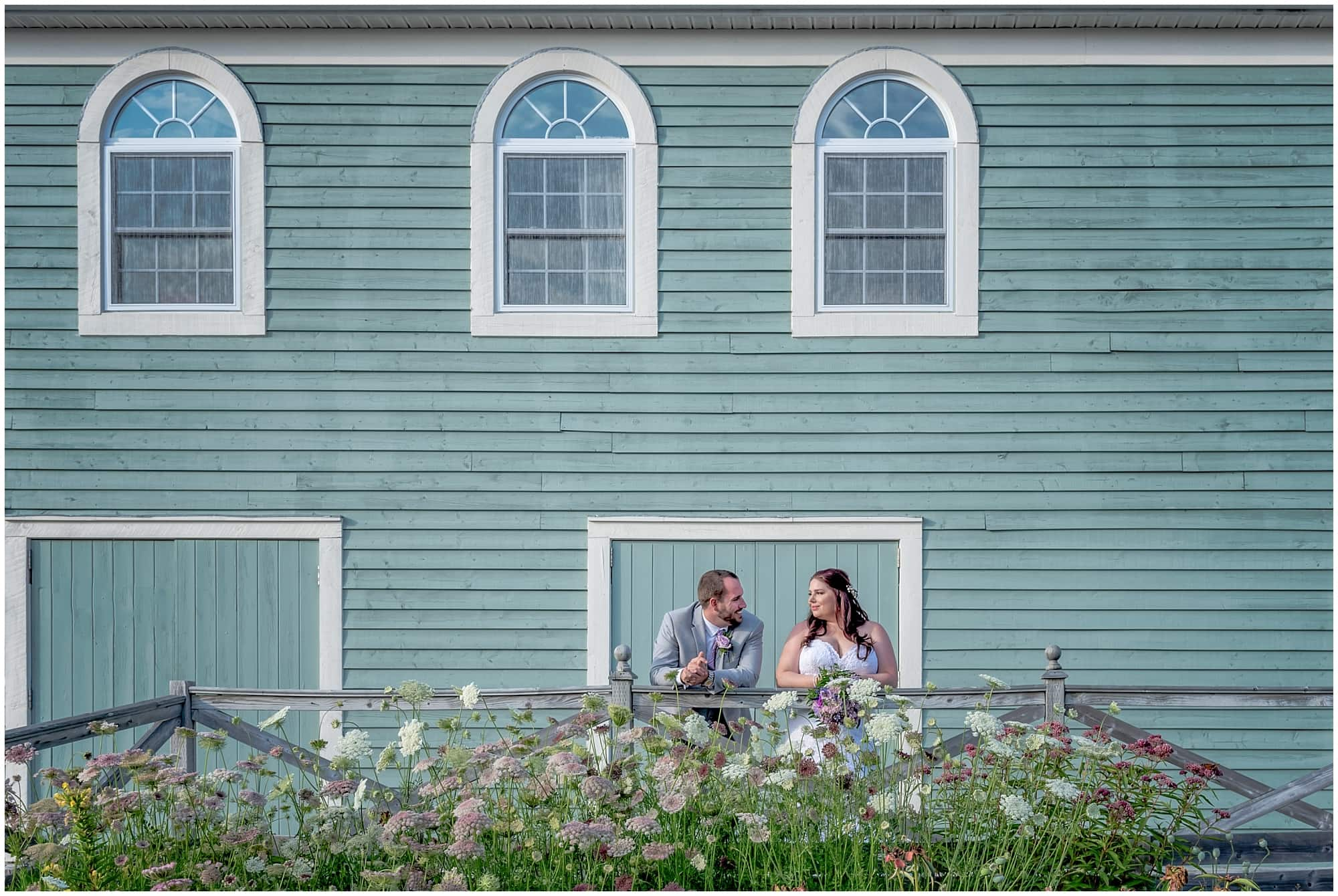 The bride and groom pose against a rustic barn style building during their White Point Beach Resort wedding photos.