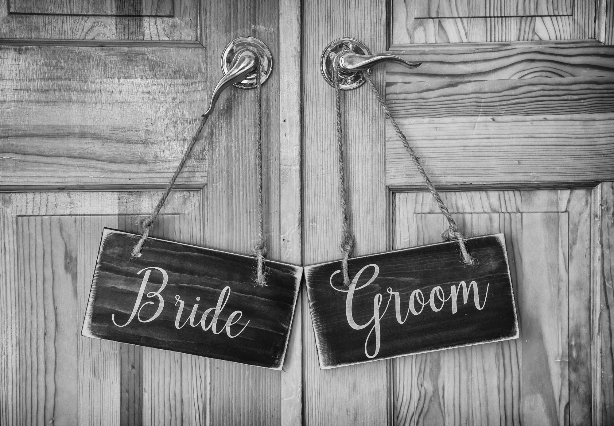 Bride and groom wooden signs for chairs at a wedding.