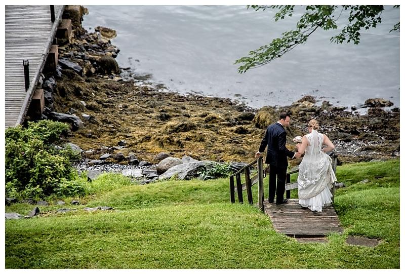 The bride and groom walk towards a wharf at Saraguay House for wedding photos.