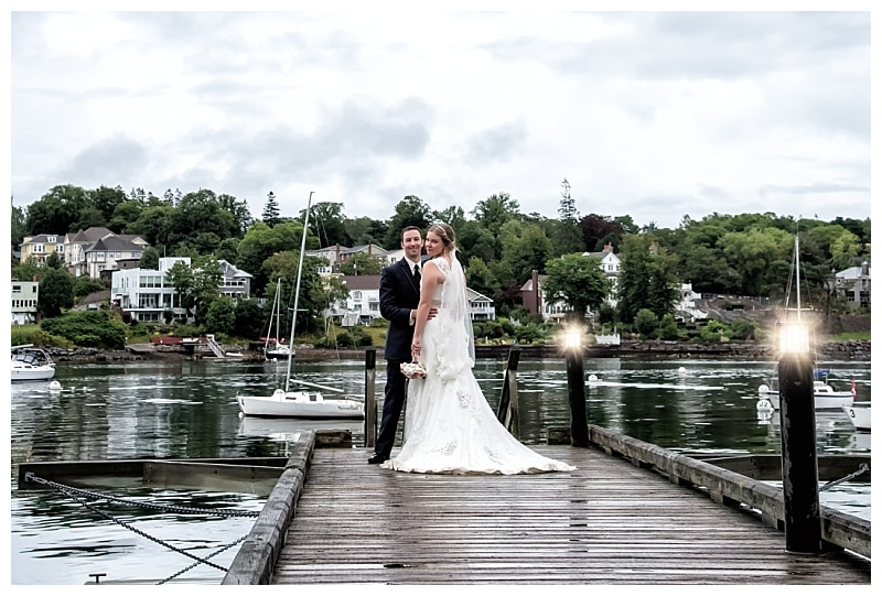 The bride and groom pose for wedding photos on a wharf during a Saraguay House Wedding in Halifax, NS.