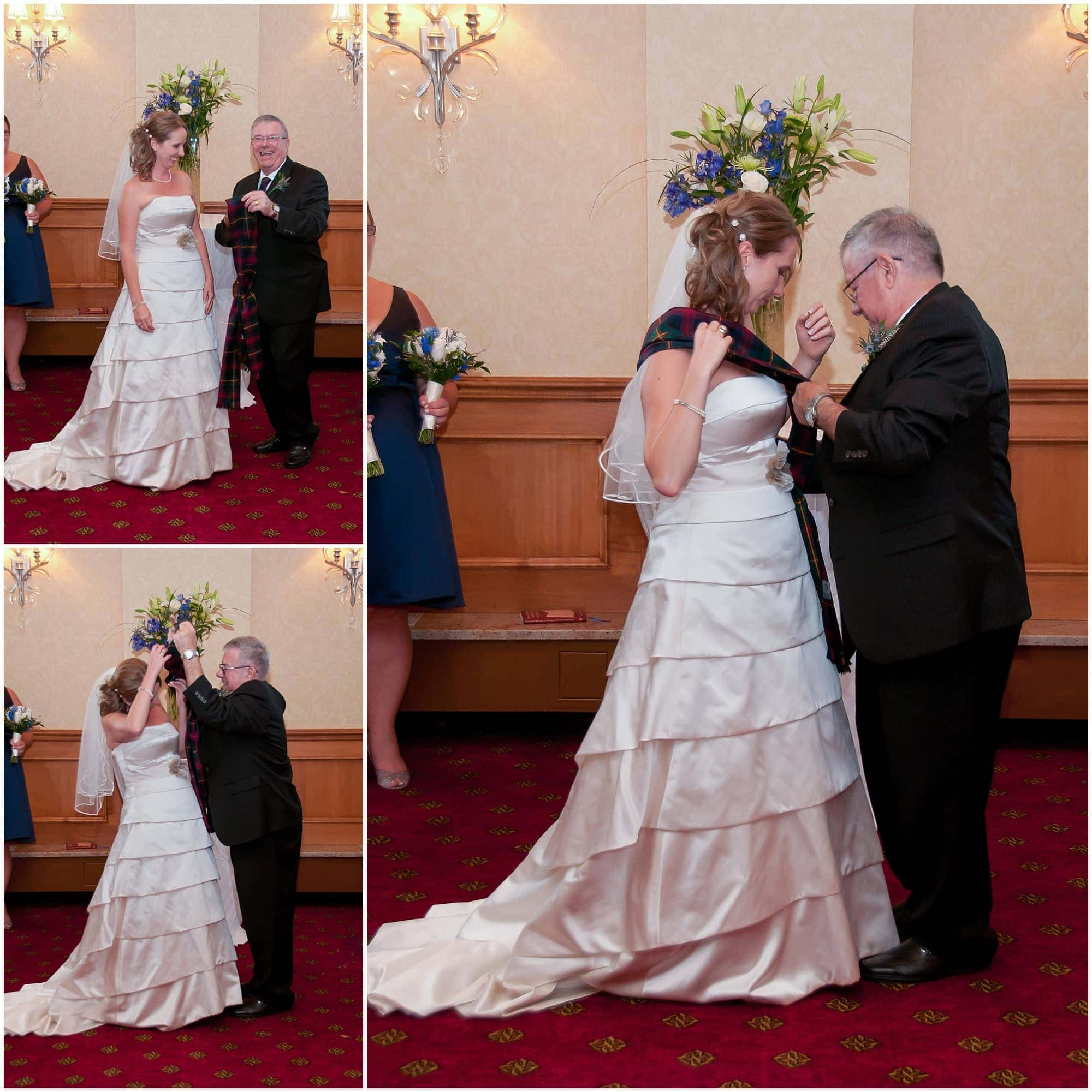 The father of the groom pinning the tartan sash on the bride's wedding dress at the Halifax Marriott Harbourfront Hotel in Nova Scotia.