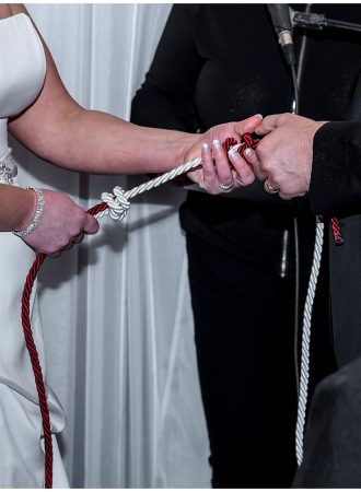 The bride and groom tie a fishermans knot or lovers knot during their wedding ceremony at the Lower Deck Tap Room in Halifax, NS.