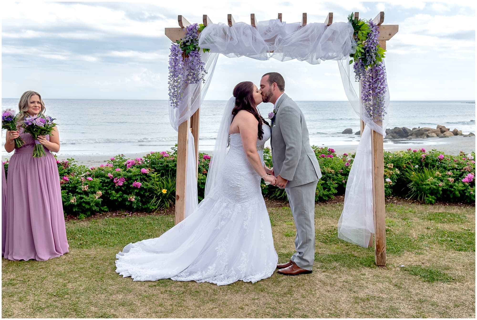 The bride and groom have their first kiss under a beautiful wedding arch during their ceremony at the White Point Beach Resort in Nova Scotia.