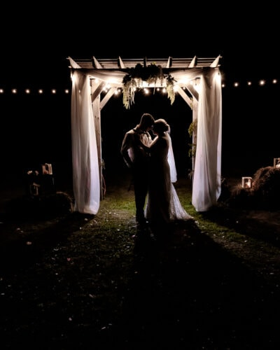 The bride and groom pose for a night silhouette portrait at their wedding at the barn at sadie belle farm.