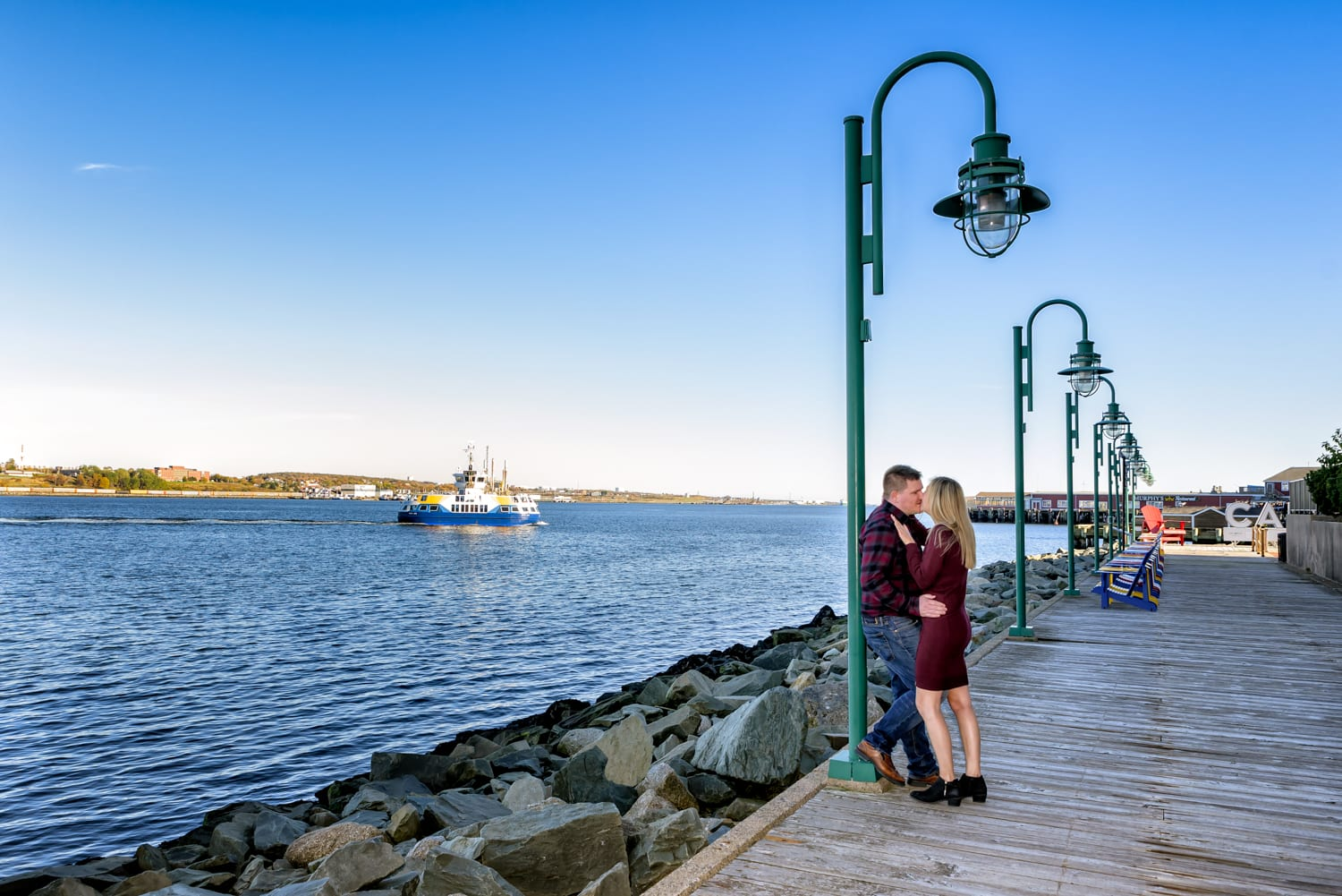 A cute couple pose on the halifax waterfront with the Halifax ferry in the background for their engagement photos.
