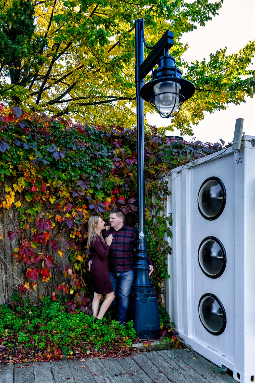 A cute couple pose for their engagement photos under a street light in downtown Halifax NS.