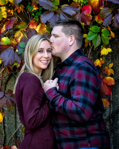 Cute couple poses for their engagement shoot surrounded by autumn leaves in the Historic Properties in Halifax, NS.