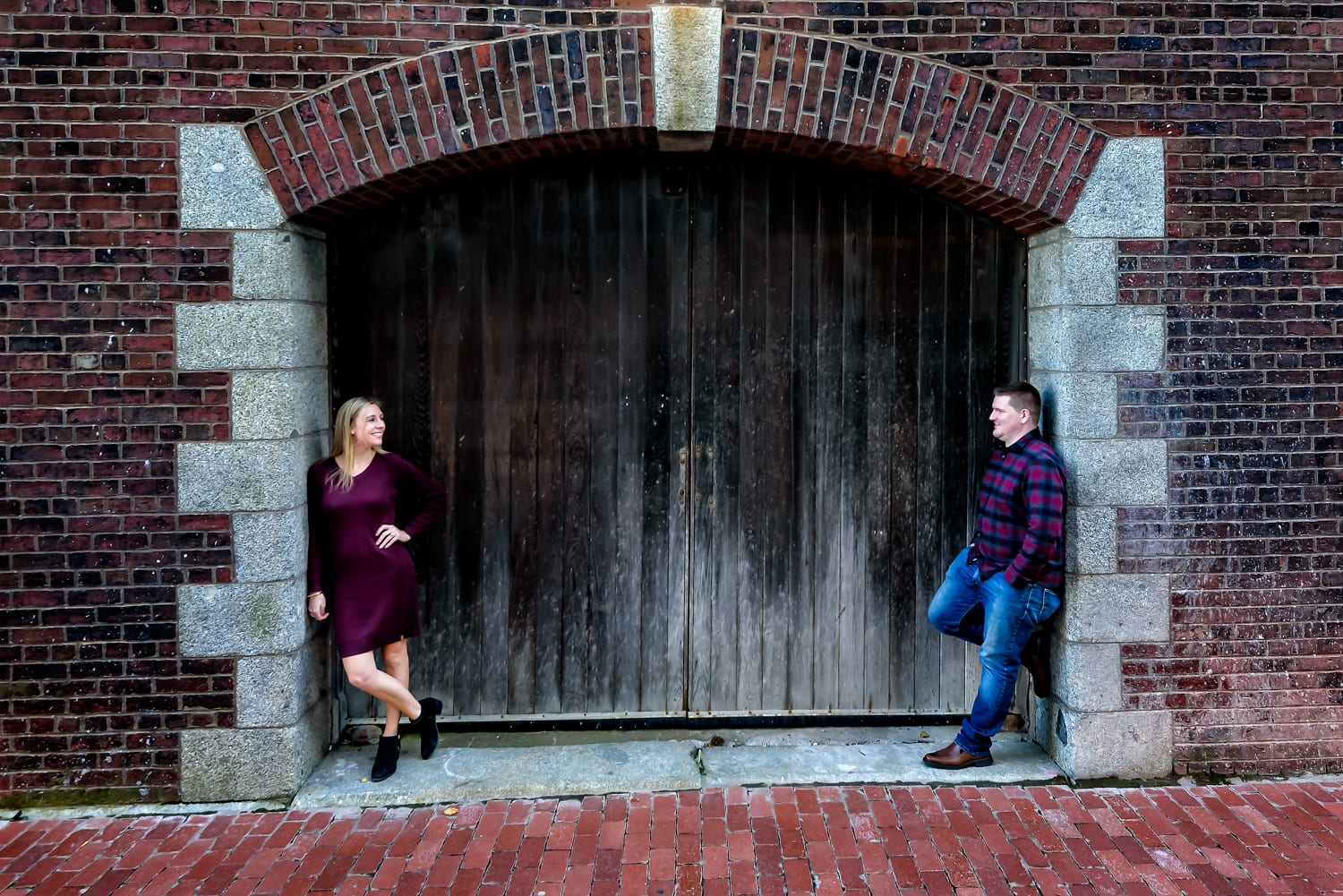 Cute couple in love pose for their urban style engagement photos on the Halifax waterfront.