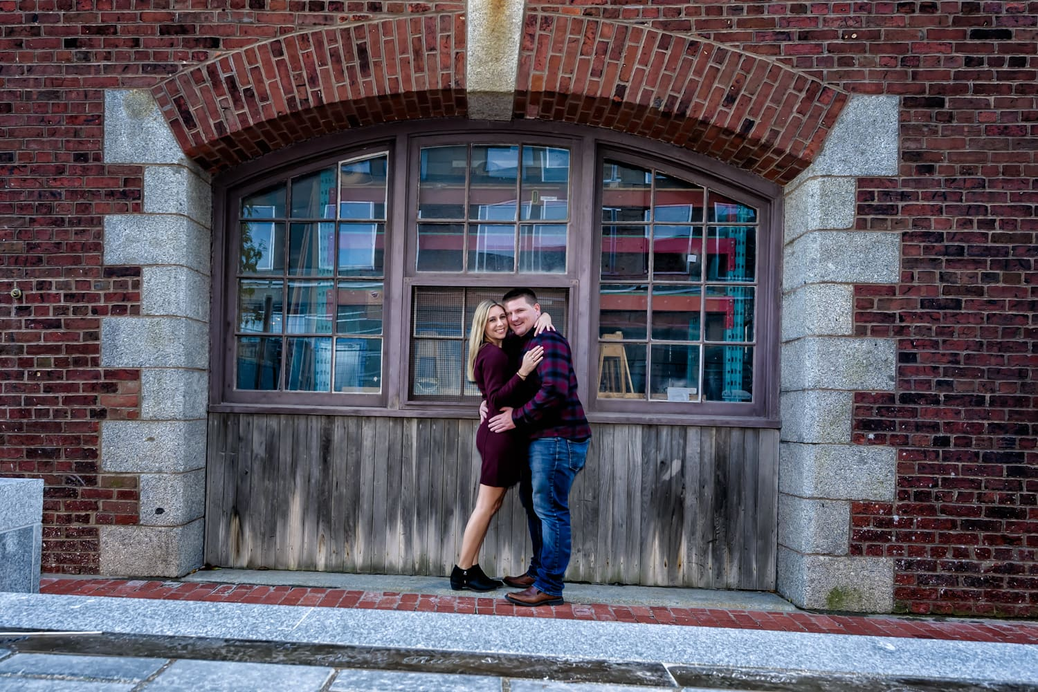 Cute couple in love pose for their engagement photos in downtown Halifax on the waterfront.