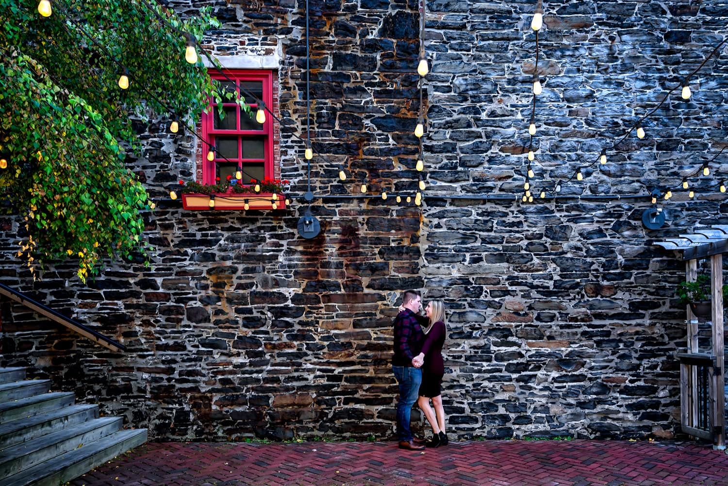 A couple in love pose for their urban style engagement photos on the MacKelvie Restaurant balcony in Halifax.