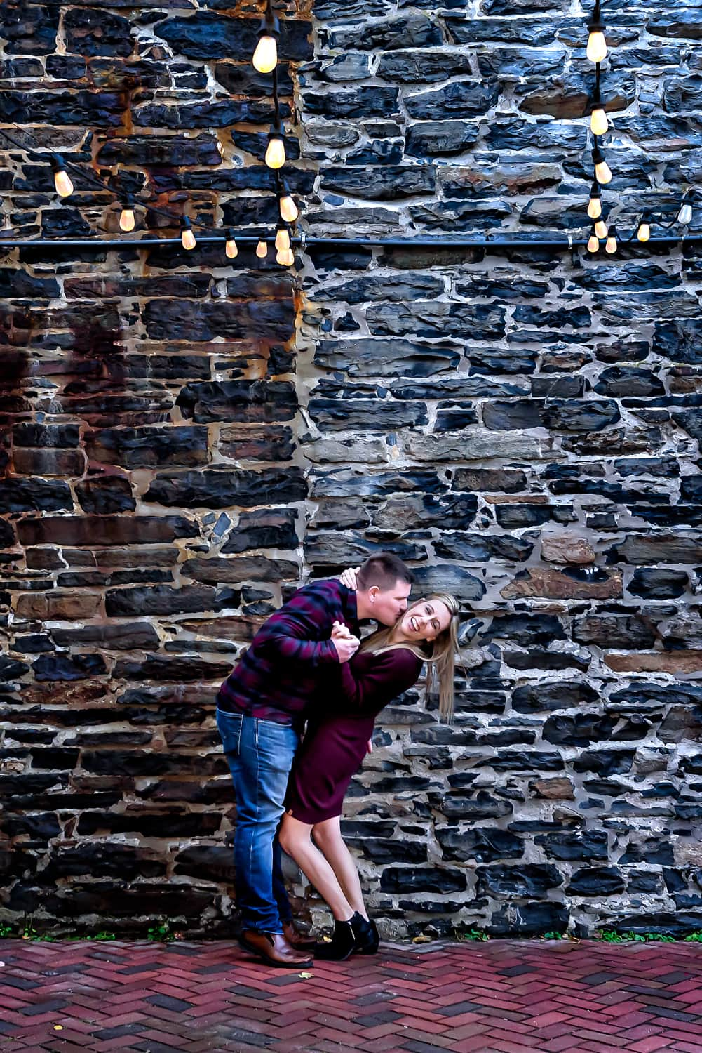 A cute couple plays during their urban style engagement photos on the Halifax waterfront.