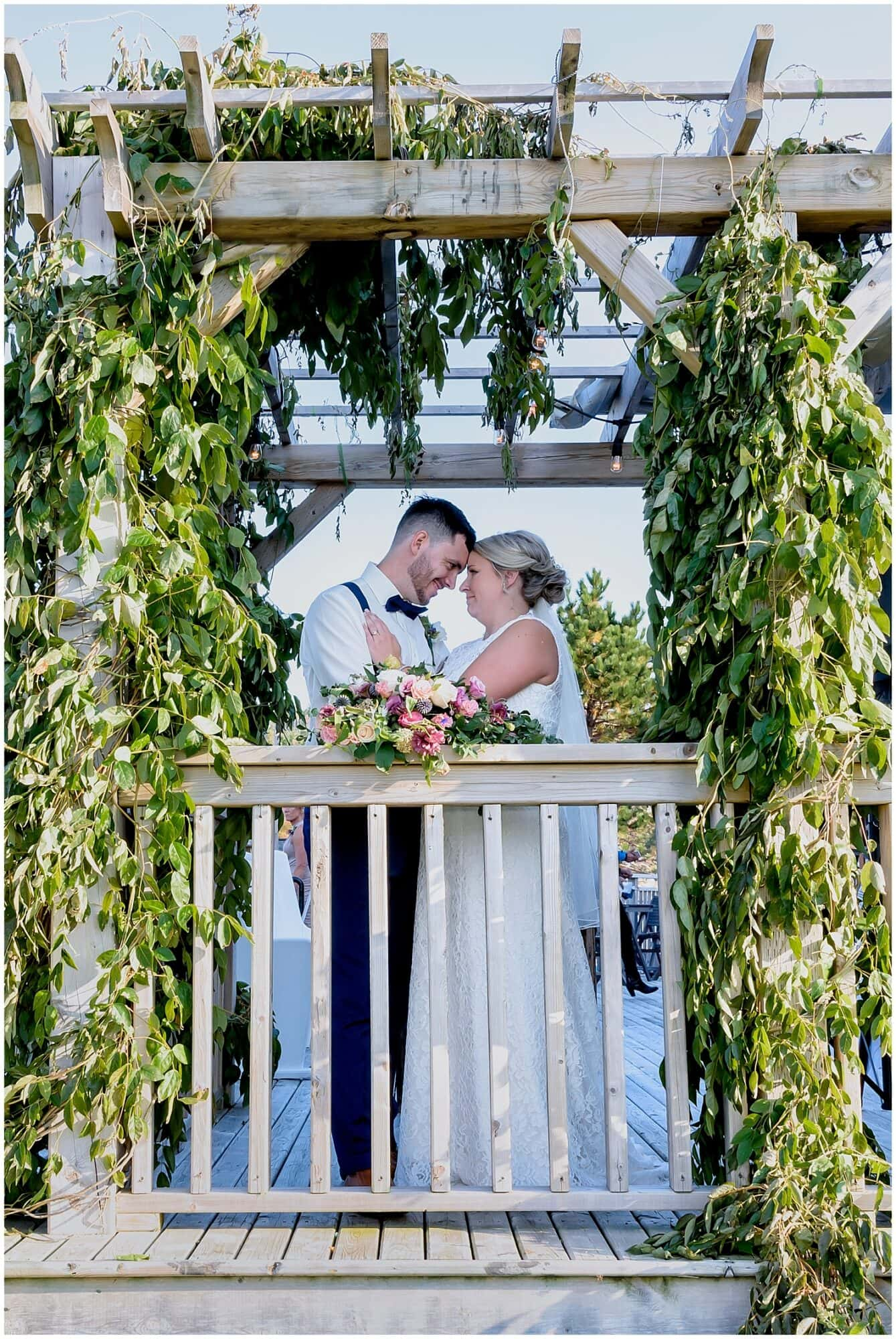 The bride and groom pose for wedding photos among the veins on the balcony at the Barn at Sadie Belle Farm in NS.