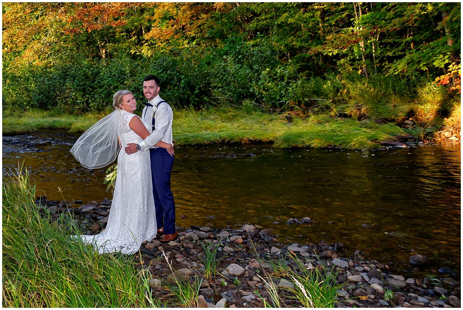 The bride and groom pose for their wedding photos by a meandering river at the barn at Sadie Belle Farm in Hantsport NS.