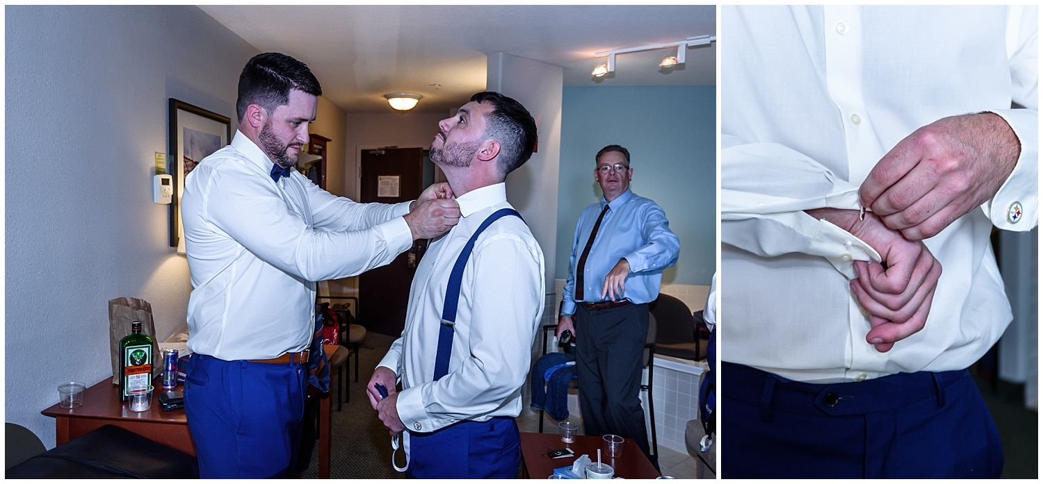 The groom getting help from a groomsmen to put his bow tie and cufflinks on during his wedding day prep at the Super 8 in Windsor NS.