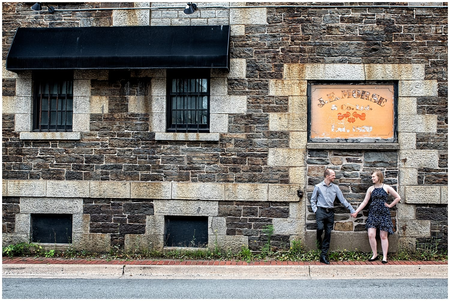 A newly engaged couple holds hands during their engagement photos at the Historic Properties in Halifax NS.