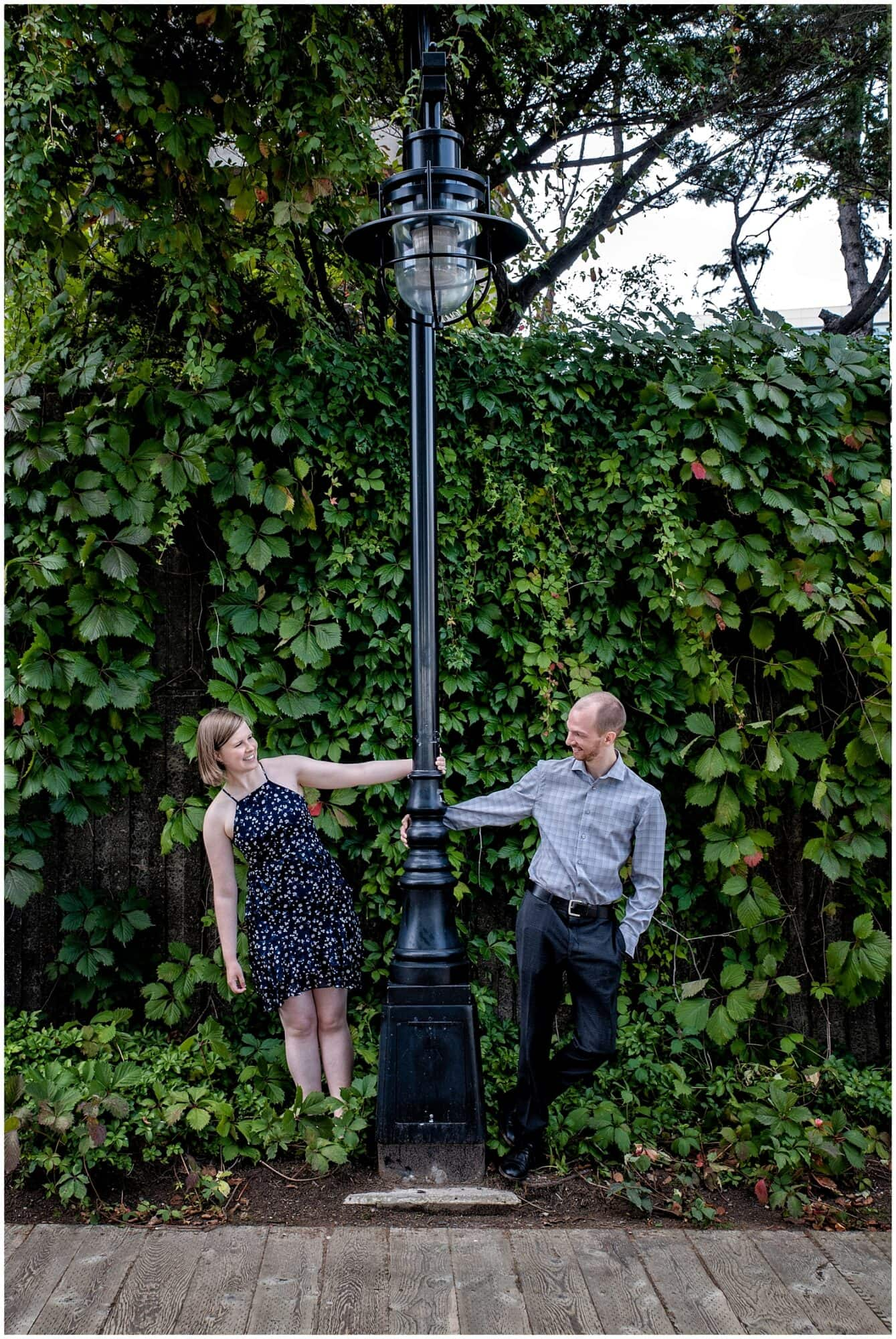 A newly engaged couple hold on to a street lamp while gazing at each other during their engagement photos at Historic Properties in Halifax NS.