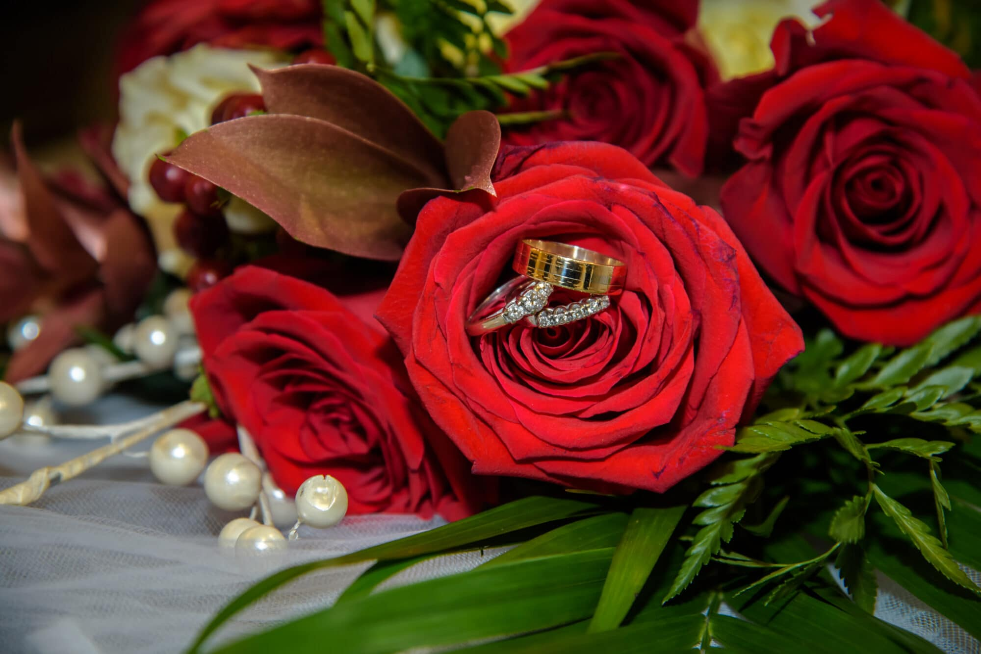 The bridal wedding bouquet of red roses with the wedding rings.