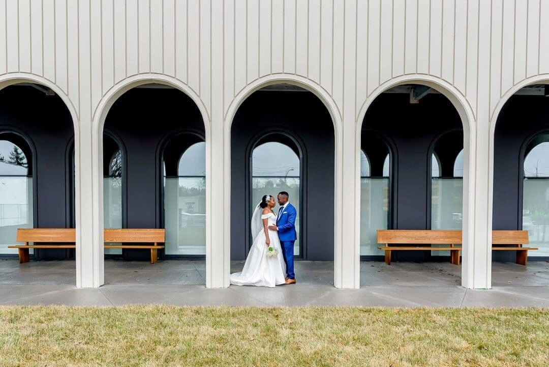 The bride and groom stand under an archway at the Cedar Events Center in Halifax during their wedding photos.